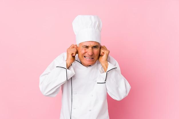 Midden oude geïsoleerde kokmens behandelend oren met handen.