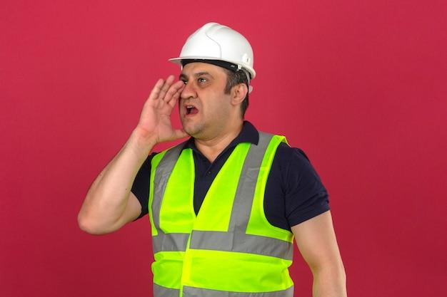 Midden oude mens die bouw geel vest draagt en veiligheidshelm die iets schreeuwt en handen dichtbij zijn geopende mond over geïsoleerde roze muur houdt