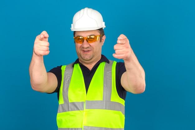 Midden oude mens die bouw geel vest en veiligheidshelm draagt en met wijsvinger richt die over geïsoleerde blauwe muur glimlacht