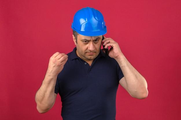 Midden oude mens die poloshirt en veiligheidshelm dragen die op mobiele telefoon met het ernstige concept van het gezichtsprobleem spreken over geïsoleerde roze muur