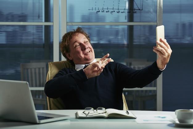Midden oude mens die selfies nemen bij zijn bureau