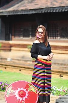 Midden oude thaise dame in kleurrijk noordelijk thais stijlkostuum op openluchttoeristplaats in chiang mai lanna thailand