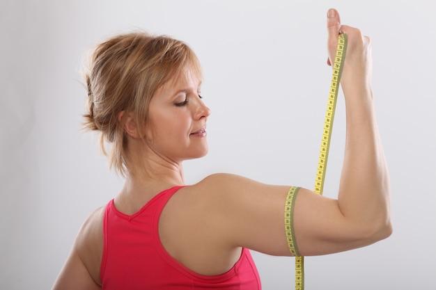 Midden sportieve tonen armen spieren glimlachend trots, fitness concept