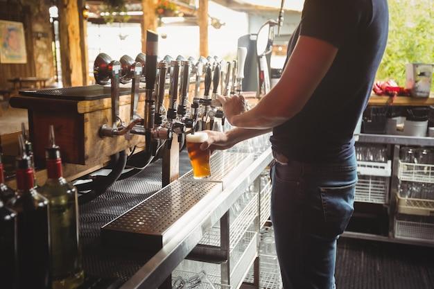 Middengedeelte van barman vullend bier van barpomp