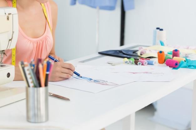 Middengedeelte van een modeontwerper die aan haar ontwerpen werkt