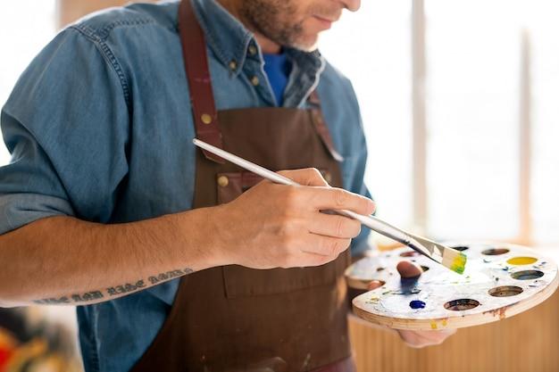 Middengedeelte van hedendaagse schilder in schort met palet met gemengde kleuren en penseel tijdens het werk