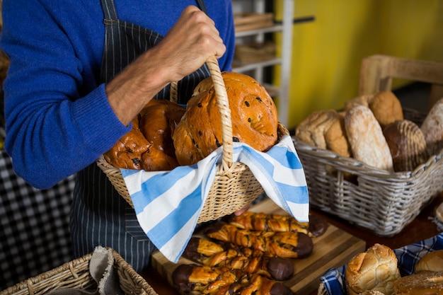 Middengedeelte van het personeel met een rieten mand met brood aan het loket