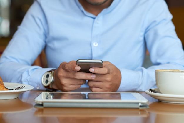 Middengedeelte van onherkenbare ondernemer die tijdens een pauze sms-berichten verzendt