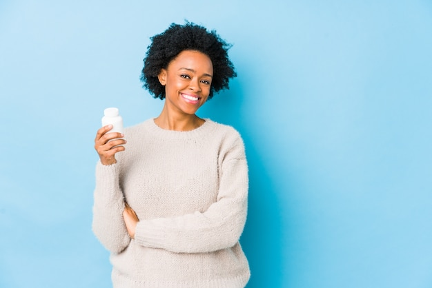 Middenleeftijd afrikaanse amerikaanse vrouw die vitaminefles glimlachen houden zeker met gekruiste wapens.