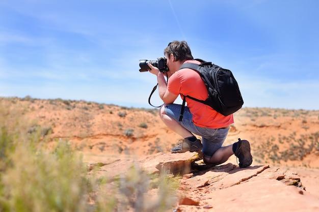 Middenleeftijdsfotograaf die foto met professionele digitale camera in openlucht nemen