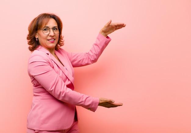 Middenleeftijdsvrouw die, gelukkig, positief en tevreden glimlachen, voorwerp of concept op exemplaarruimte houden tonen of tonen tegen roze muur