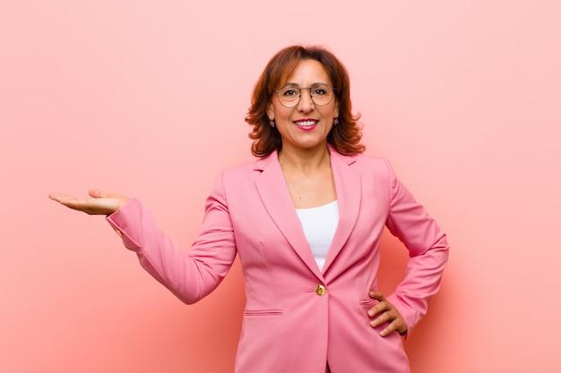 Middenleeftijdsvrouw die, zeker, succesvol en gelukkig, het tonen of idee op copyspace op de zij roze muur glimlachen voelen