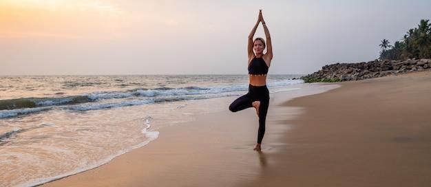 Middenleeftijdsvrouw in zwarte het doen van yoga op zandstrand in india bij zonsondergang