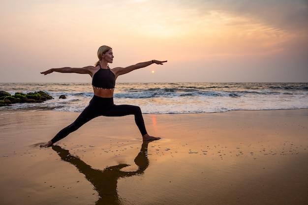 Middenleeftijdsvrouw in zwarte het doen van yoga op zandstrand