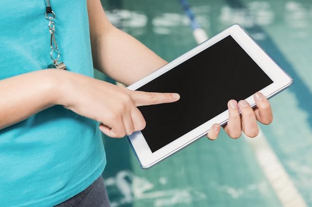 Middensectie van coach met behulp van digitale tablet aan zwembadzijde