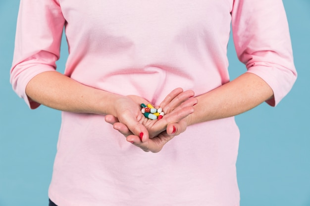 Middensectie van een vrouw die verscheidenheid van capsules in hand houdt