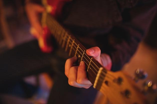 Middensectie van man gitaarspelen