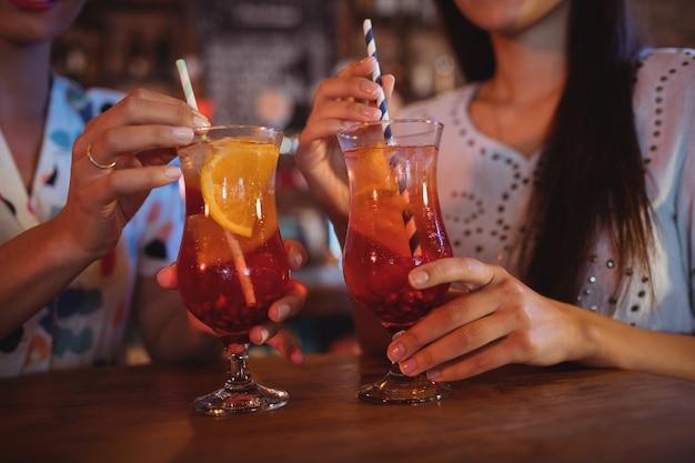 Middensectie van twee jonge vrouwen die cocktaildranken hebben
