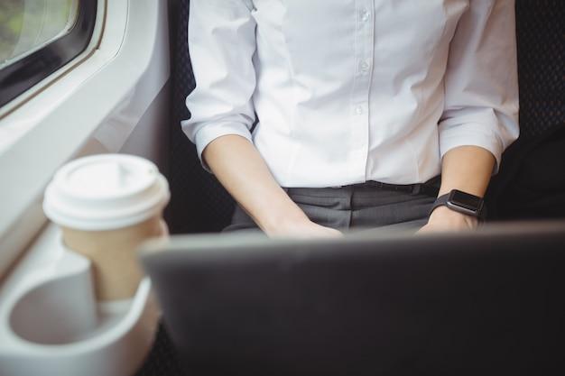 Middensectie van vrouw die laptop met behulp van