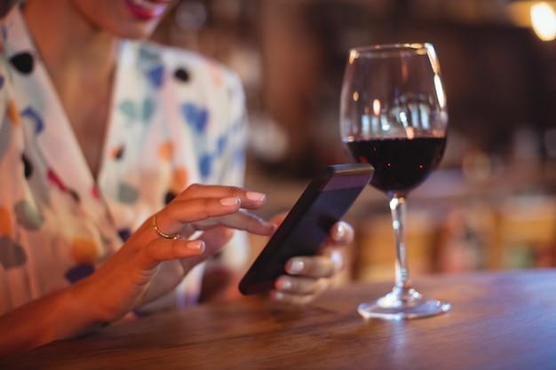 Middensectie van vrouw die mobiele telefoon met behulp van