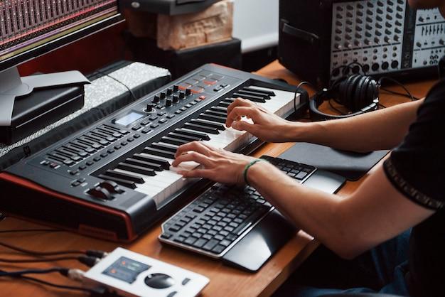 Midi-keyboard spelen. geluidstechnicus werkt en mixt muziek binnenshuis in de studio.