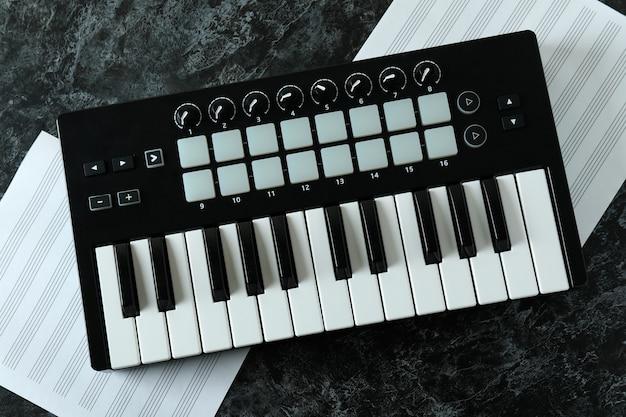 Midi-toetsenbord en muziekbladen op zwarte smokey-tafel