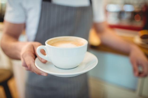 Midsection van barista dienende koffie bij winkel