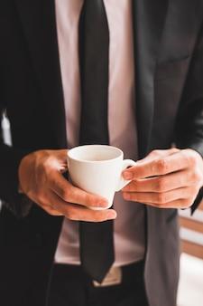 Midsection van de koffiekop van de zakenmanholding