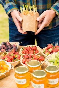 Midsection van de wortelen van de mensenholding over aardbeien voor verkoop
