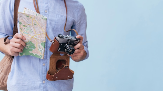 Midsection van mannelijke de holdingscamera en kaart die van de reizigersfotograaf zich tegen blauwe achtergrond bevinden