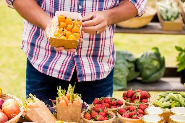 Midsection van mensen verkopende tomaten