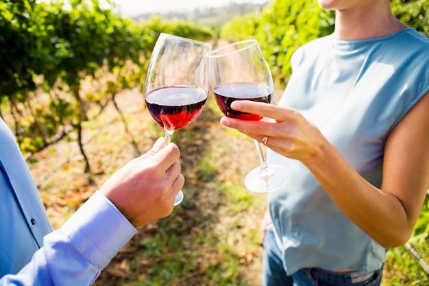 Midsection van paar roosterende wijnglazen