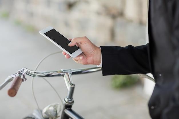 Midsection van zakenman die cellphone gebruikt