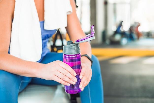 Midsectionmening van de fles van het de holdingswater van de vrouwenhand in gymnastiek
