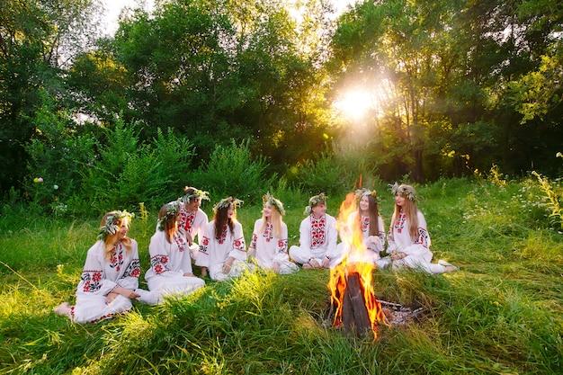 Midzomer, groep jongeren van slavische uiterlijk zitten rond een kampvuur.