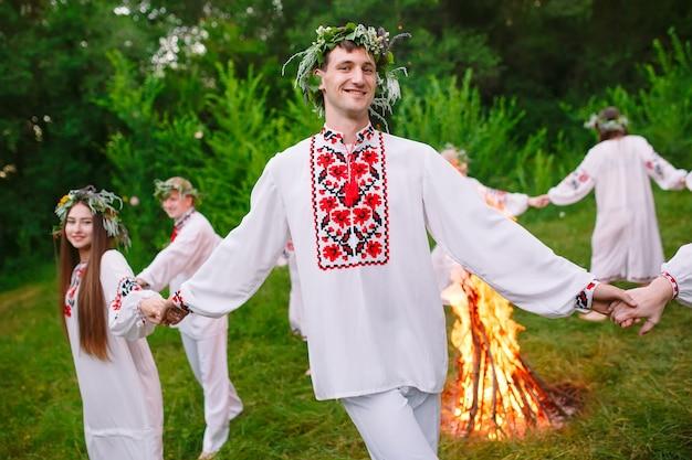 Midzomer, jonge mensen in slavische kleding draaien rond een vuur in de midzomer,.