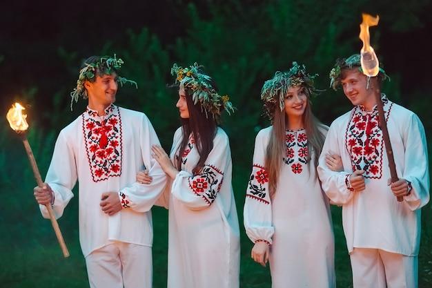 Midzomer, jongeren in dezelfde slavische kostuums houden fakkels met vuur vast.