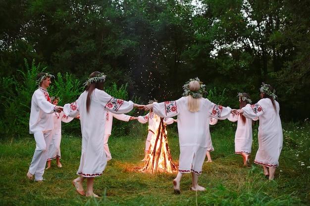 Midzomer. jongeren in slavische kleren dansen rond een kampvuur in het bos.
