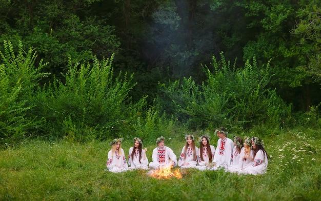 Midzomer. jongeren in slavische kleren zitten in het bos bij het vuur.