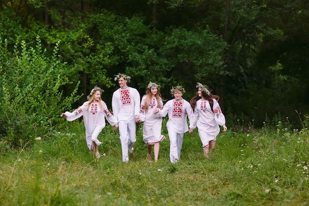 Midzomer. mensen lopen in de natuur in slavische kleding.