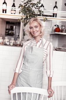 Mijn bakkerij. opgetogen blonde vrouw achter de stoel terwijl ze in haar bakkerij werkte