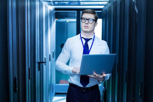 Mijn beroep. intelligente jonge werknemer die zijn laptop vasthoudt terwijl hij in het datacenter werkt