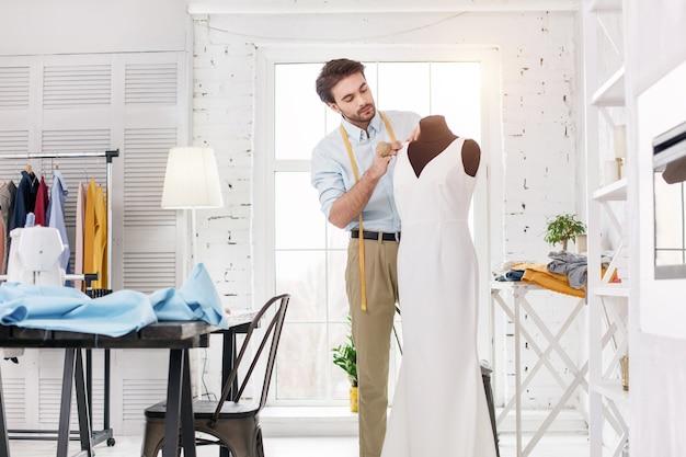 Mijn beroep. opgetogen jonge kleermaker die in zijn kantoor werkt en een nieuwe jurk maakt