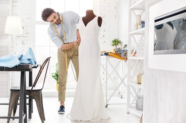 Mijn beroep. professionele jonge kleermaker die in zijn kantoor werkt en een nieuwe jurk maakt