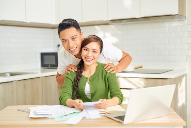 Mijn beste. liefdevolle glimlachende echtgenoot die schouders van zijn mooie vrouw in de keuken masseert