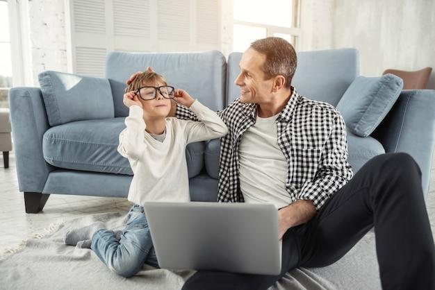 Mijn beste vriend. aardige gelukkige blonde jongen die glimlacht en een grote bril draagt en zijn vader die met zijn laptop dichtbij hem zit