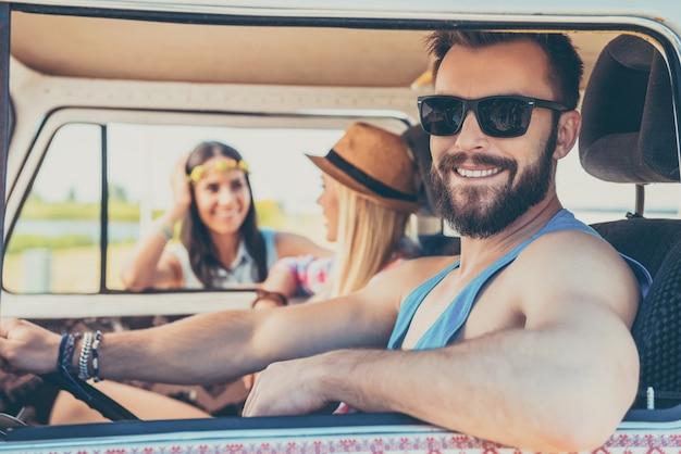 Mijn beste weekend. vrolijke jonge man zittend op de voorbank van de minibus terwijl twee jonge vrouwen op de achtergrond praten