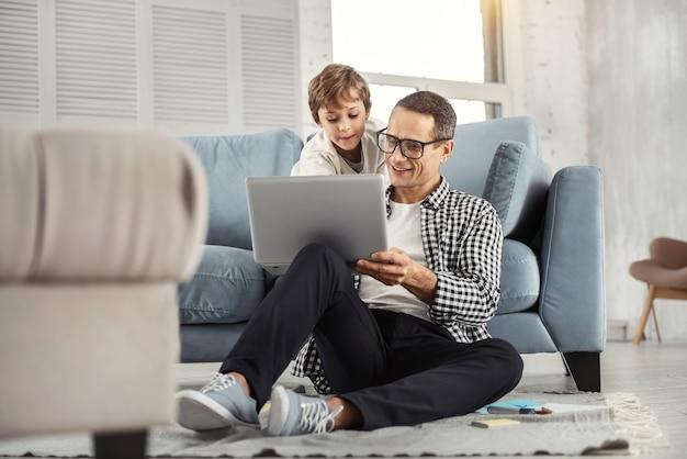 Mijn beste zoon. knappe vrolijke donkerharige vader die een bril draagt en foto's op de laptop toont aan zijn zoon en zijn zoon die achter hem zit