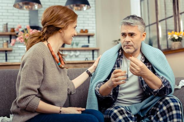 Mijn dagelijkse dosis. trieste zieke man die zijn medicijn tegen griep neemt terwijl hij naar zijn vrouw kijkt