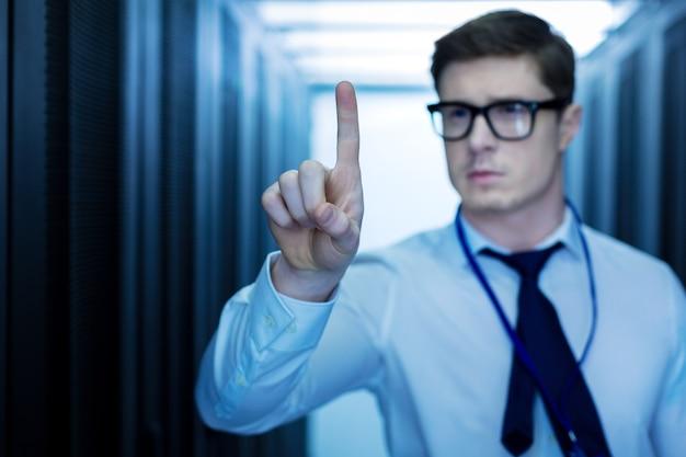 Mijn datacenter. knappe slimme man die in een datacenter werkt en met zijn vinger wijst